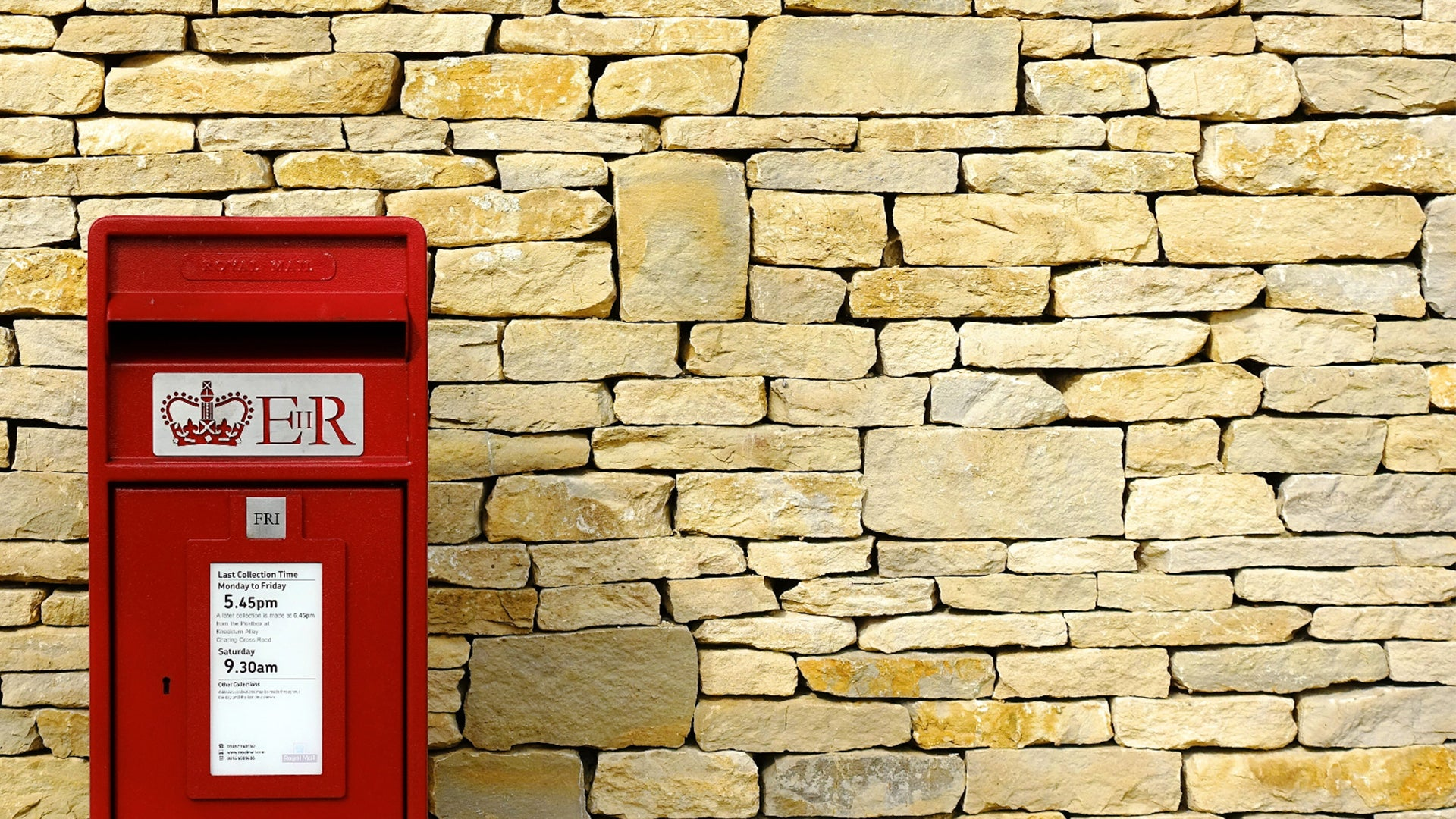 A picture of a sandstone coloured wall and a bright red postbox in front of it