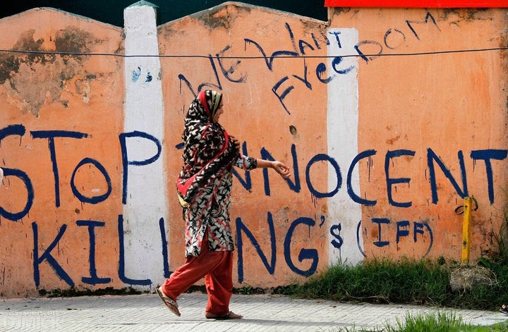 A woman walking alone in Kashmir. Slogans demanding freedom and an end to killing are painted on the orange wall behind her.