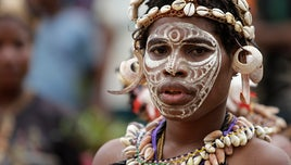 Woman in Papua New Guinea in her ritual face paint and head dress.