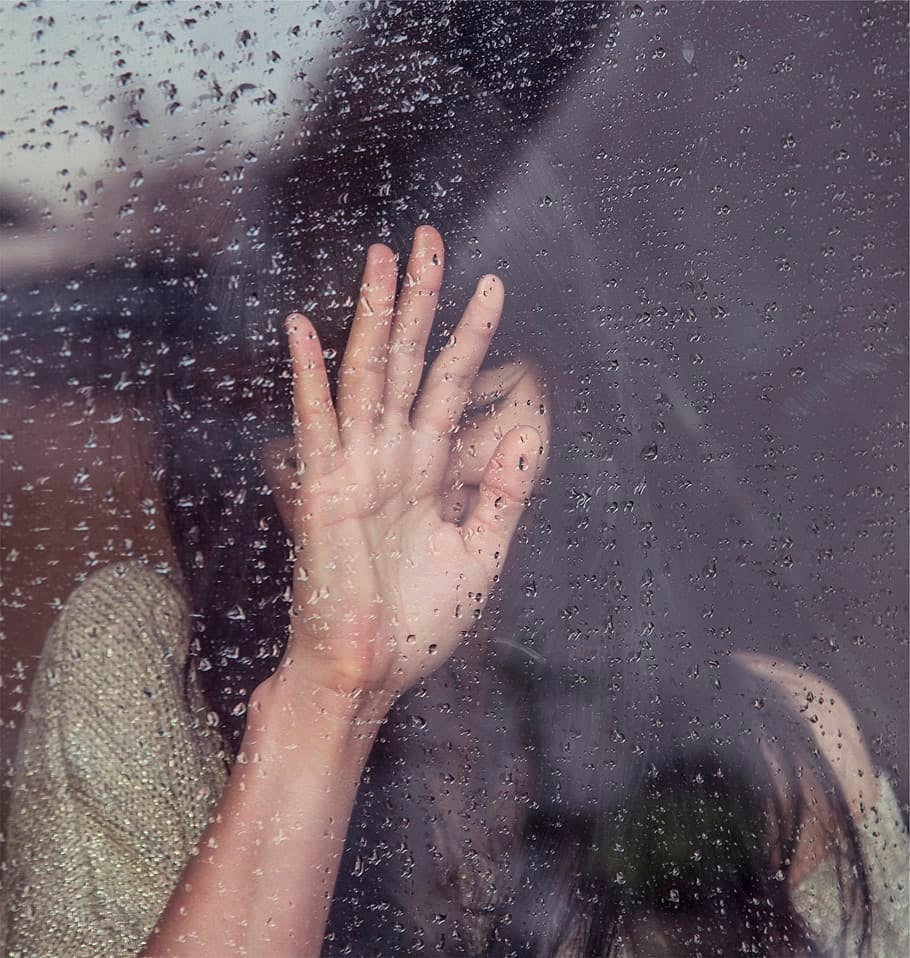 A young woman can be seen through a window. Her hand is rested on the glass, partially obscuring her face, and she appears to be crying.