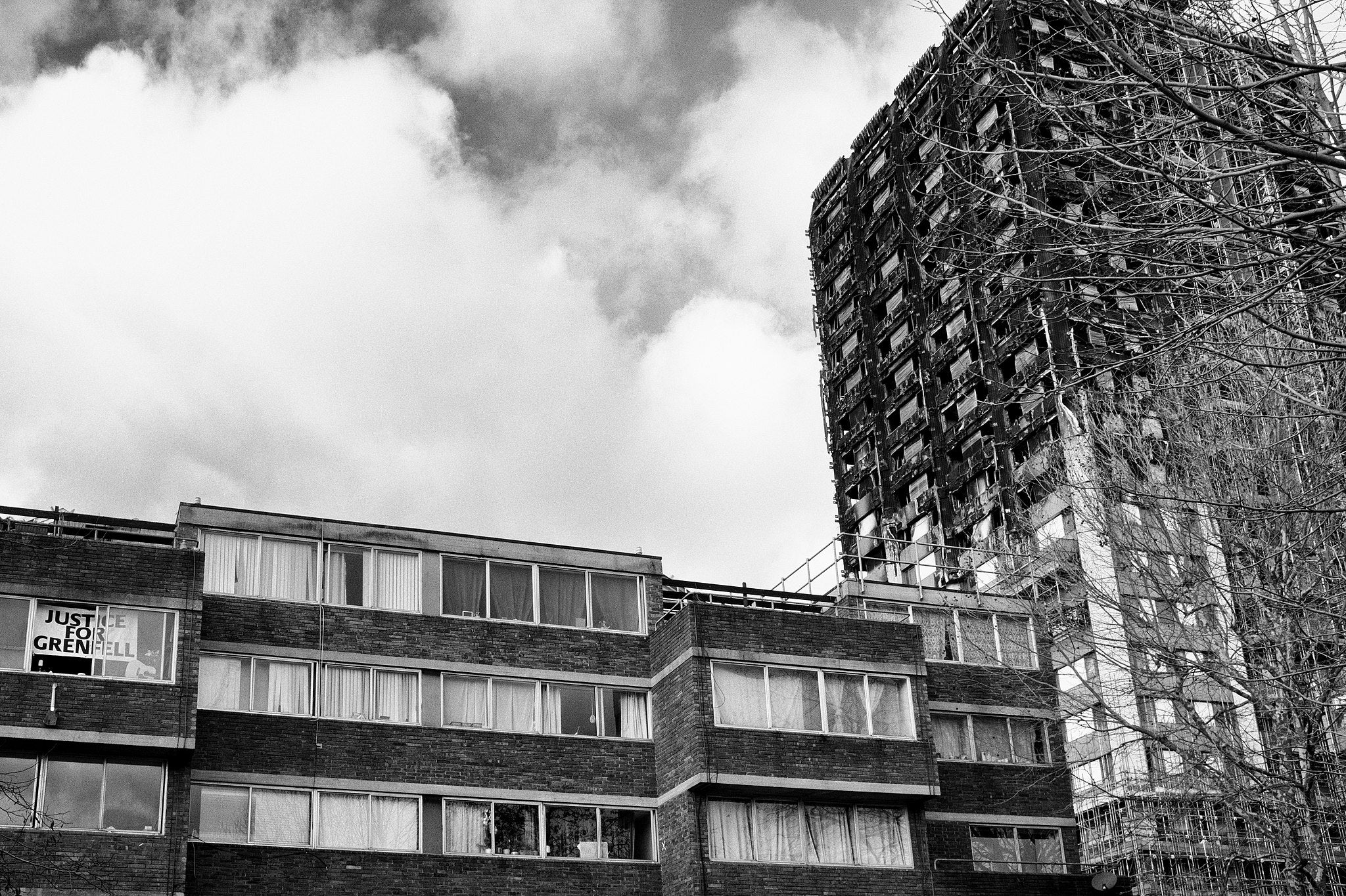 Grenfell Tower, after the fire. A 'Justice for Grenfell' poster in the window or a nearby flat.