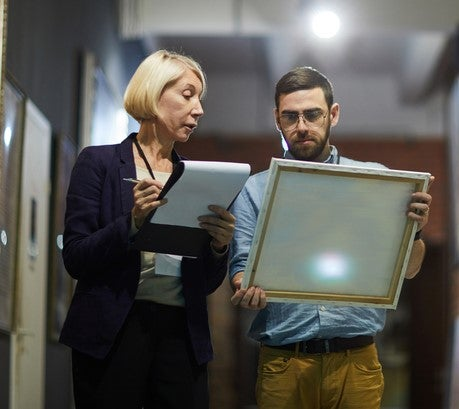A male and a female curator examining a canvas held by the man. The woman is holding a pen and a clipboard.