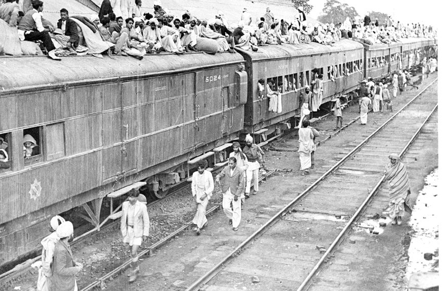 A black and white photo of a packed refugee special train at Ambala Station during the partition of India. Even the roof of the train is full of people.