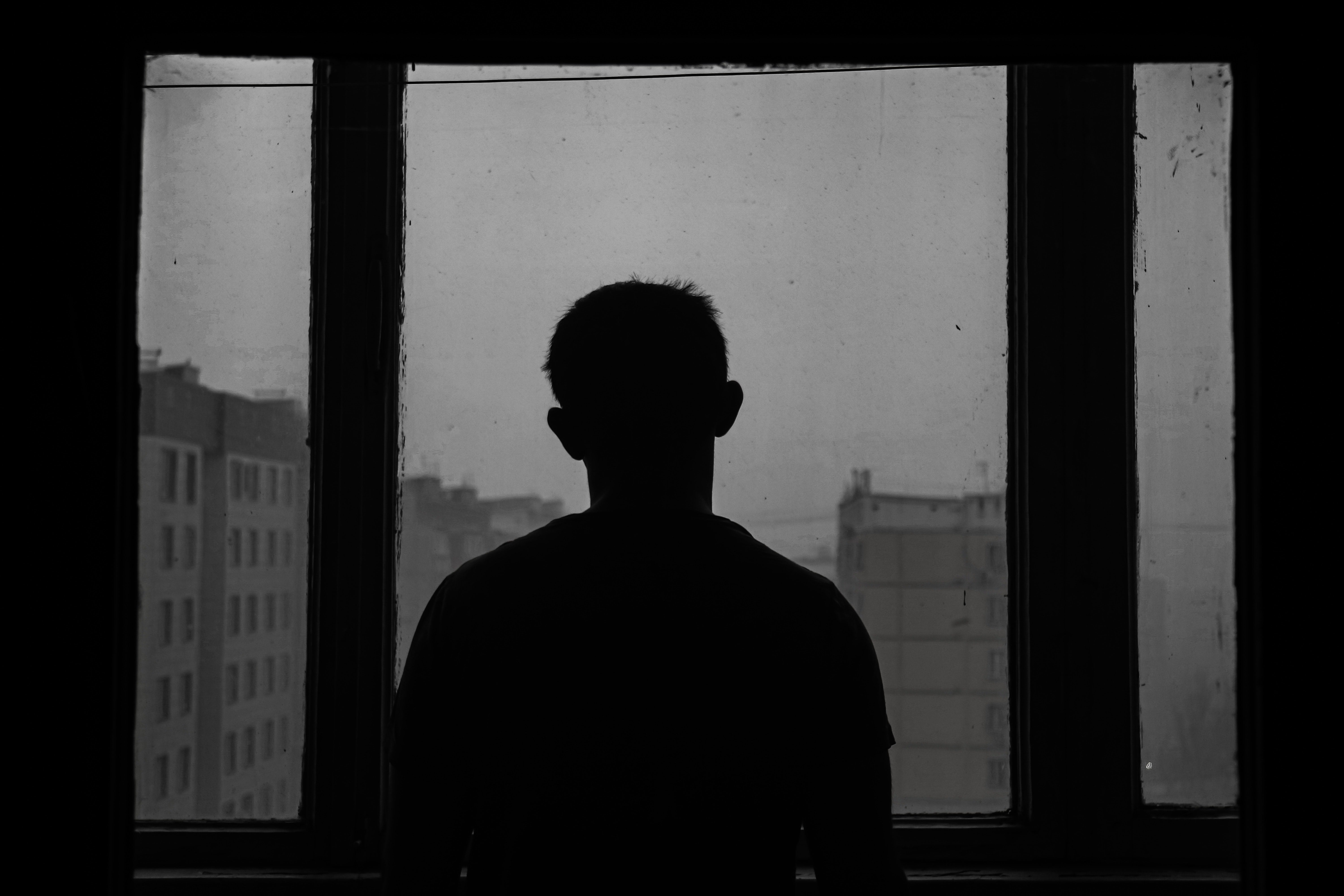 A man's silhouette looking out of a window