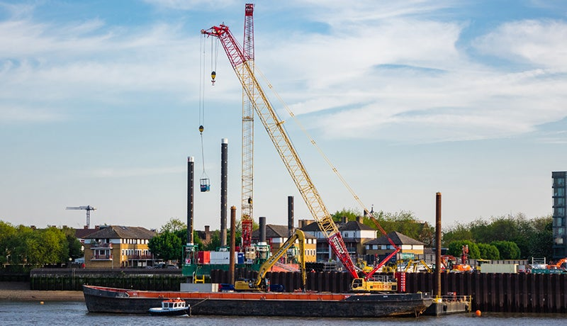 A long boat sits shoreside on the River Thames. A yellow and red crane extends upwards from it.
