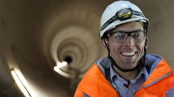 A worker in an orange coat and white hard hat smiles into the camera. We can see he is in a gigantic tunnel