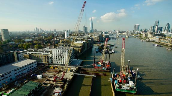 Aerial photo of the Thames in London, focusing on cranes stationed on the water. Tall buildings of the city are in the distance