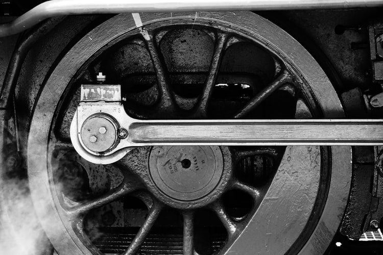 A black and white picture, featuring a close-up of the wheel of a steam train
