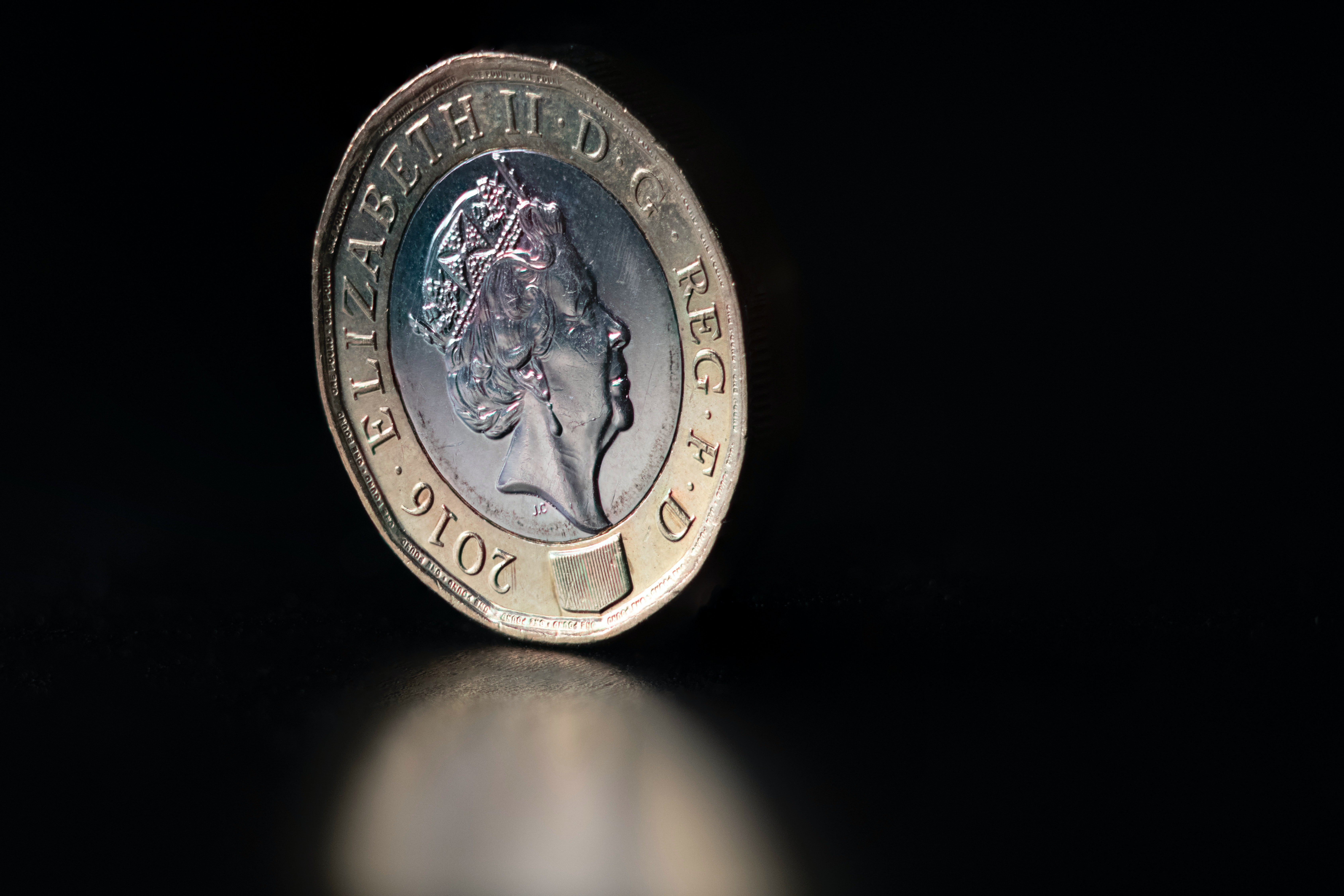 A pound coin on a black background