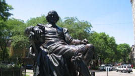 A picture of a Shakespeare statue. It presents him seated.