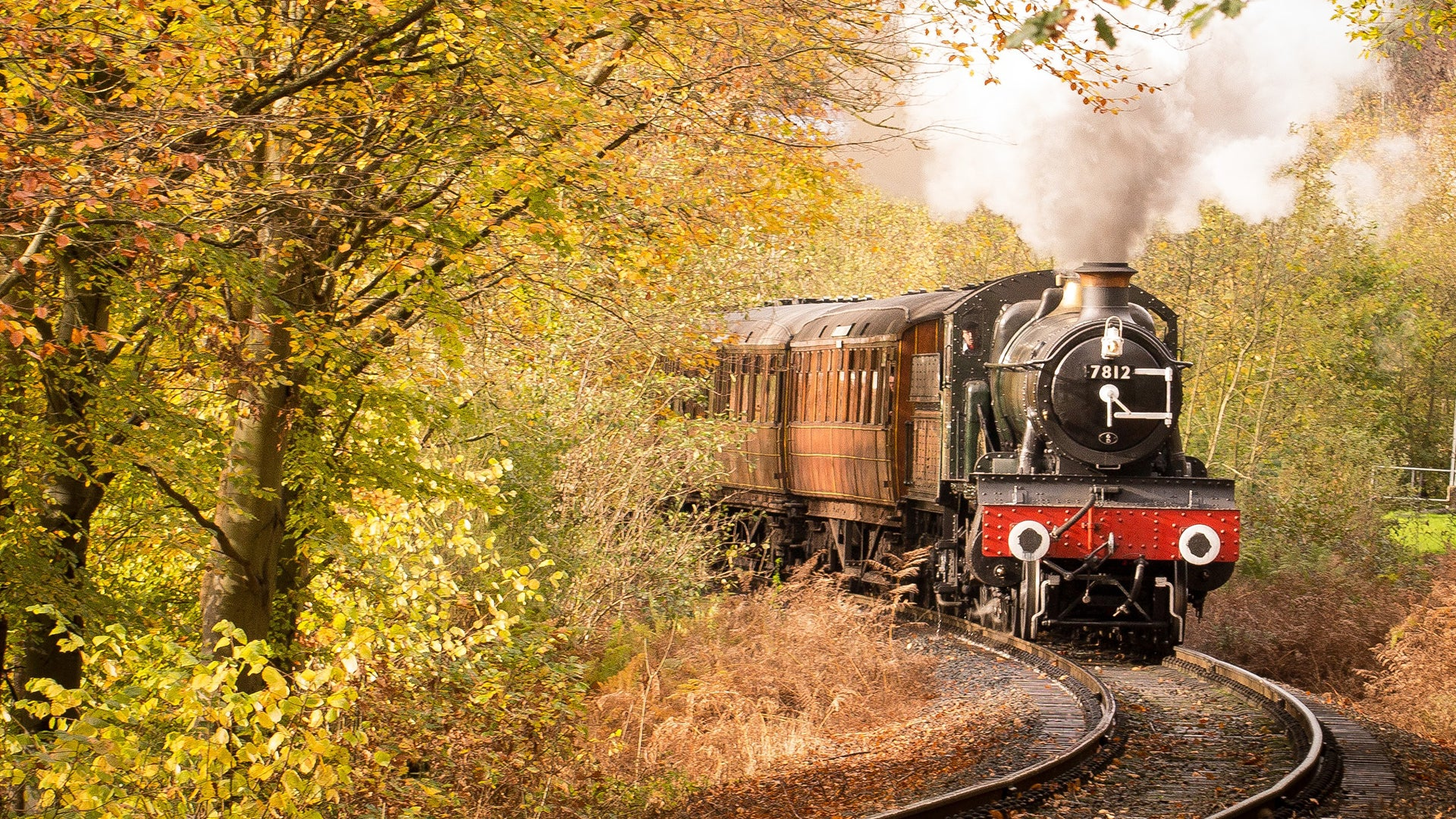 A picture of a steam train riding along a track around some trees