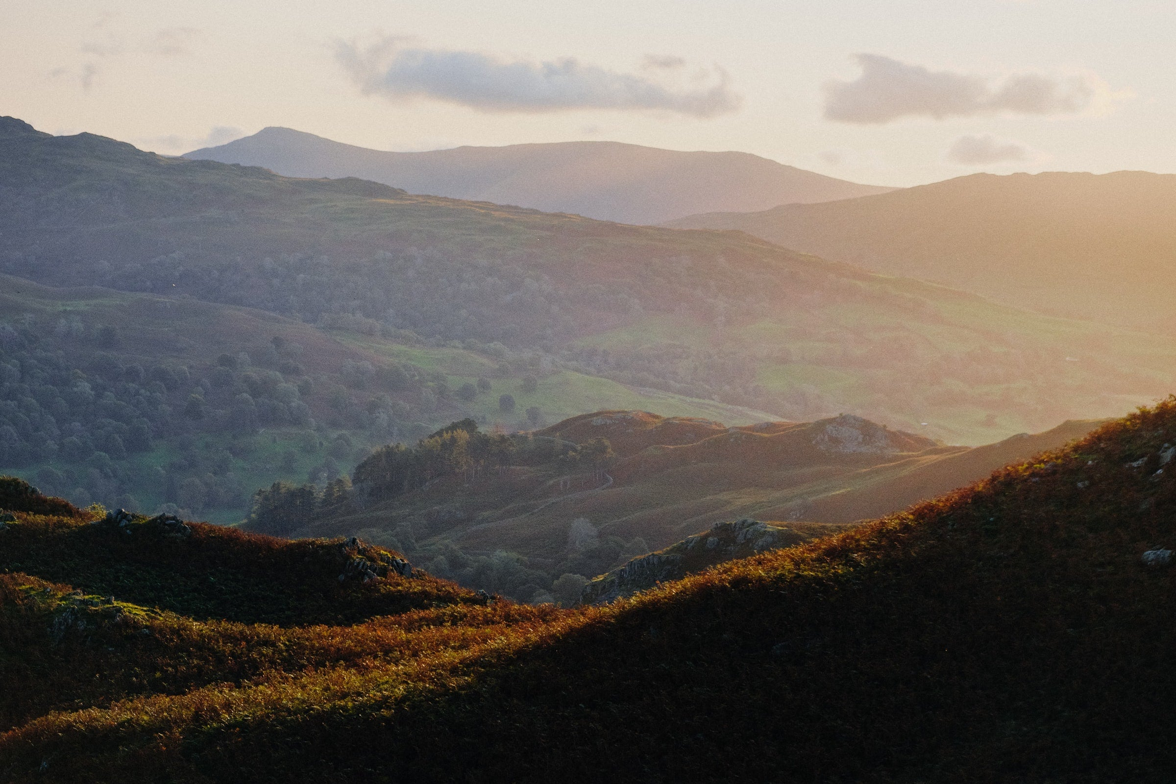 A view of green and brown rolling hills, with sunlight breaking across the landscape