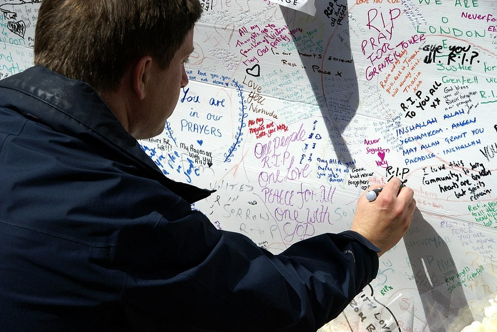 A man writes on Grenfell tribute wall