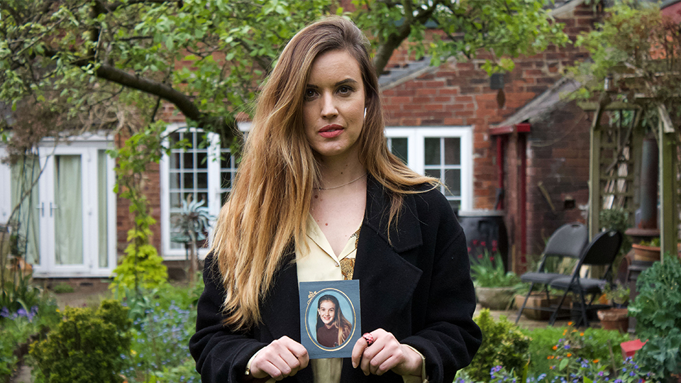 A picture of Charlie holding a photograph of herself from when she was in school.