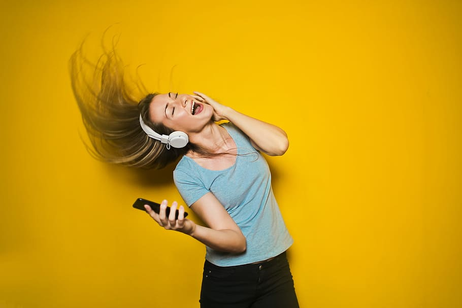 A woman wearing headphones and enjoying music playing from her phone