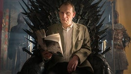 Presenter Andrew Marr sitting on a realisation of the Iron Throne from the Game of Thrones TV series. He is holding an open copy of a book that inspired the series, written by George RR Martin.