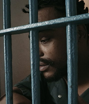 A man sits behind bars in a jail cell