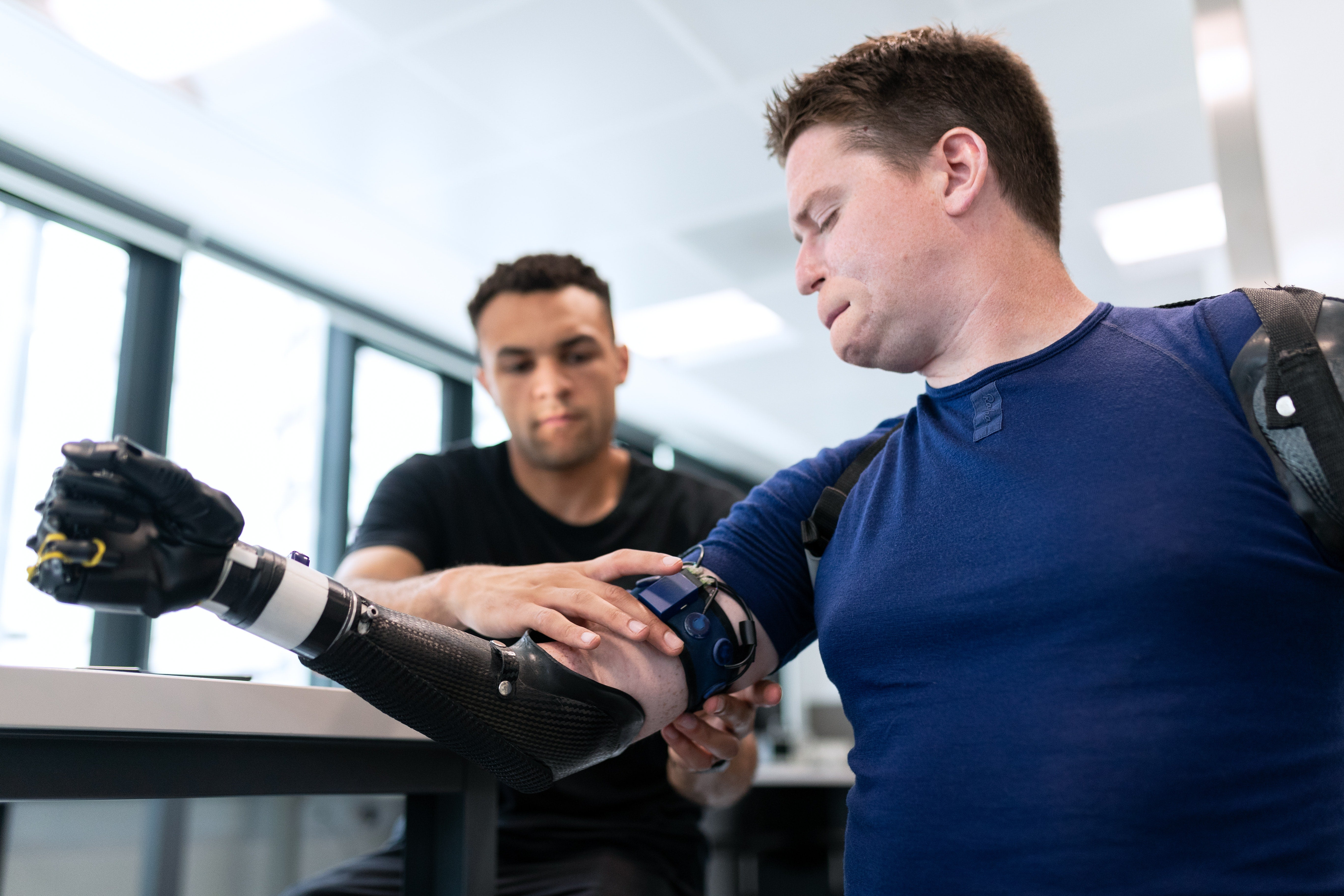 Man fitting a bionic arm to disabled patient