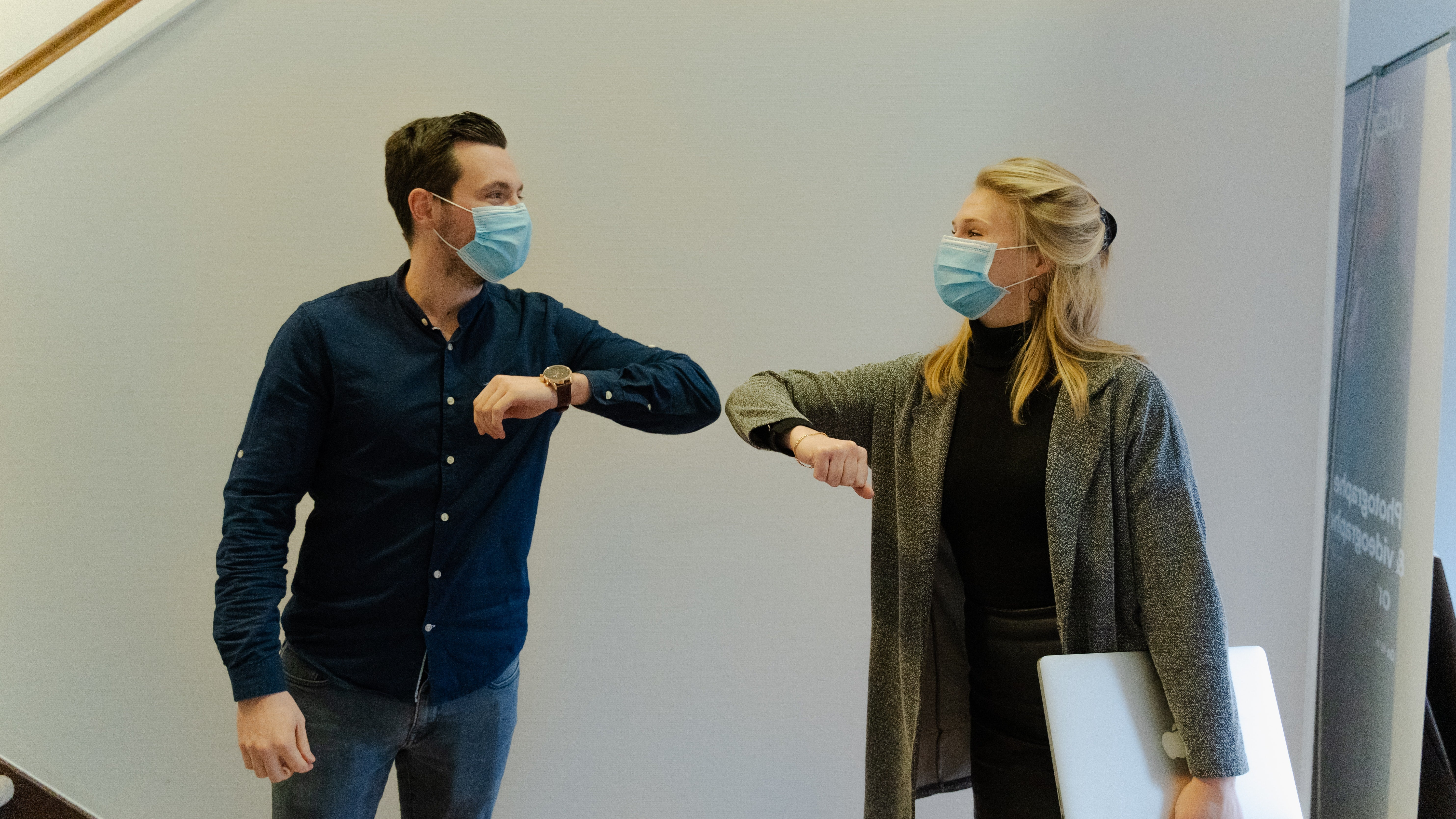 Two people in face masks doing an elbow bump