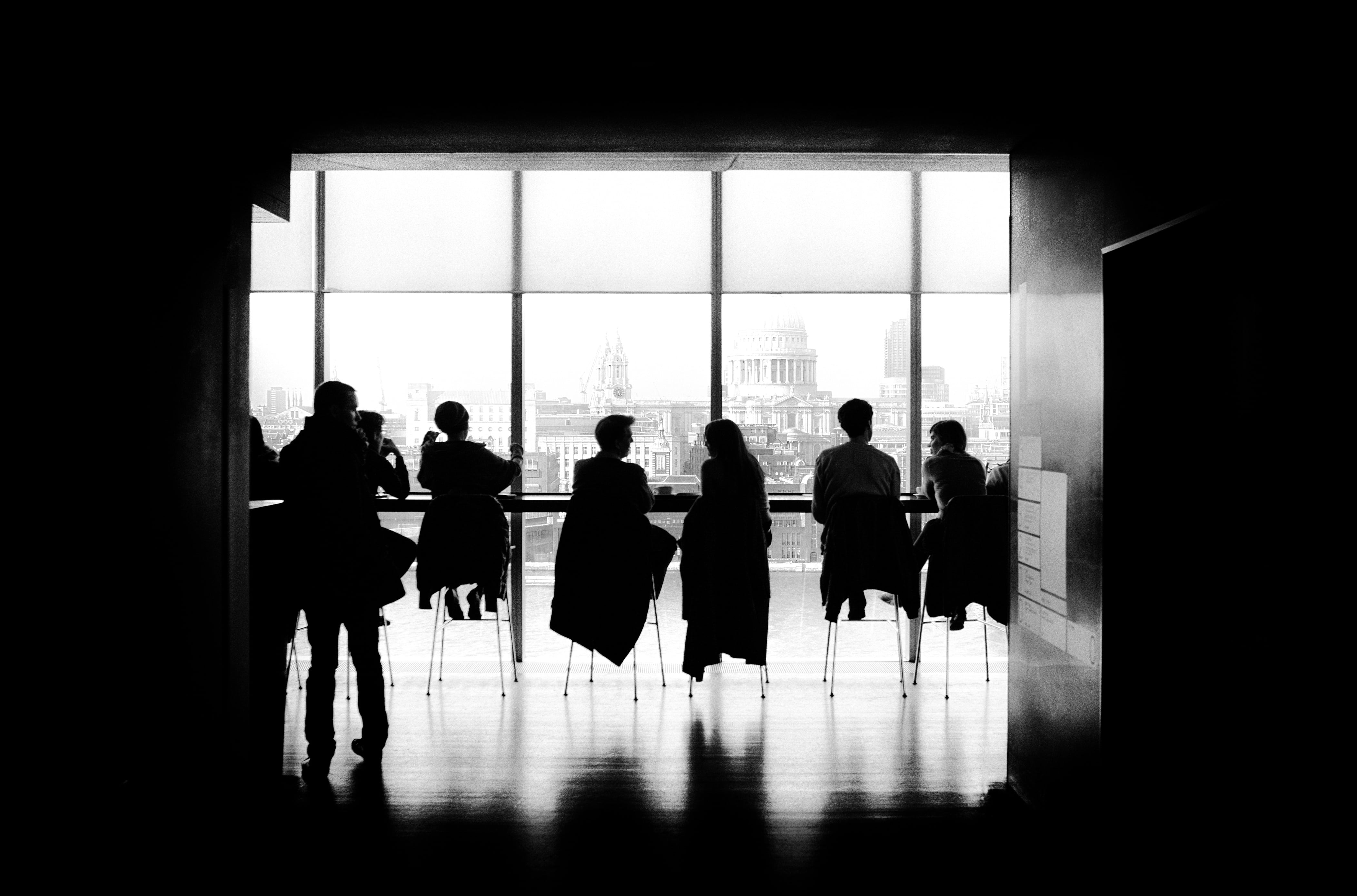 A black and white photo of people sat in a conference room. Only their silhouettes are visible. It is several floors up and Saint Paul's cathedral is visible outside the window