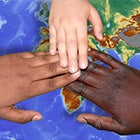 A photograph of three people's hands touching in a show of union over a map of the world