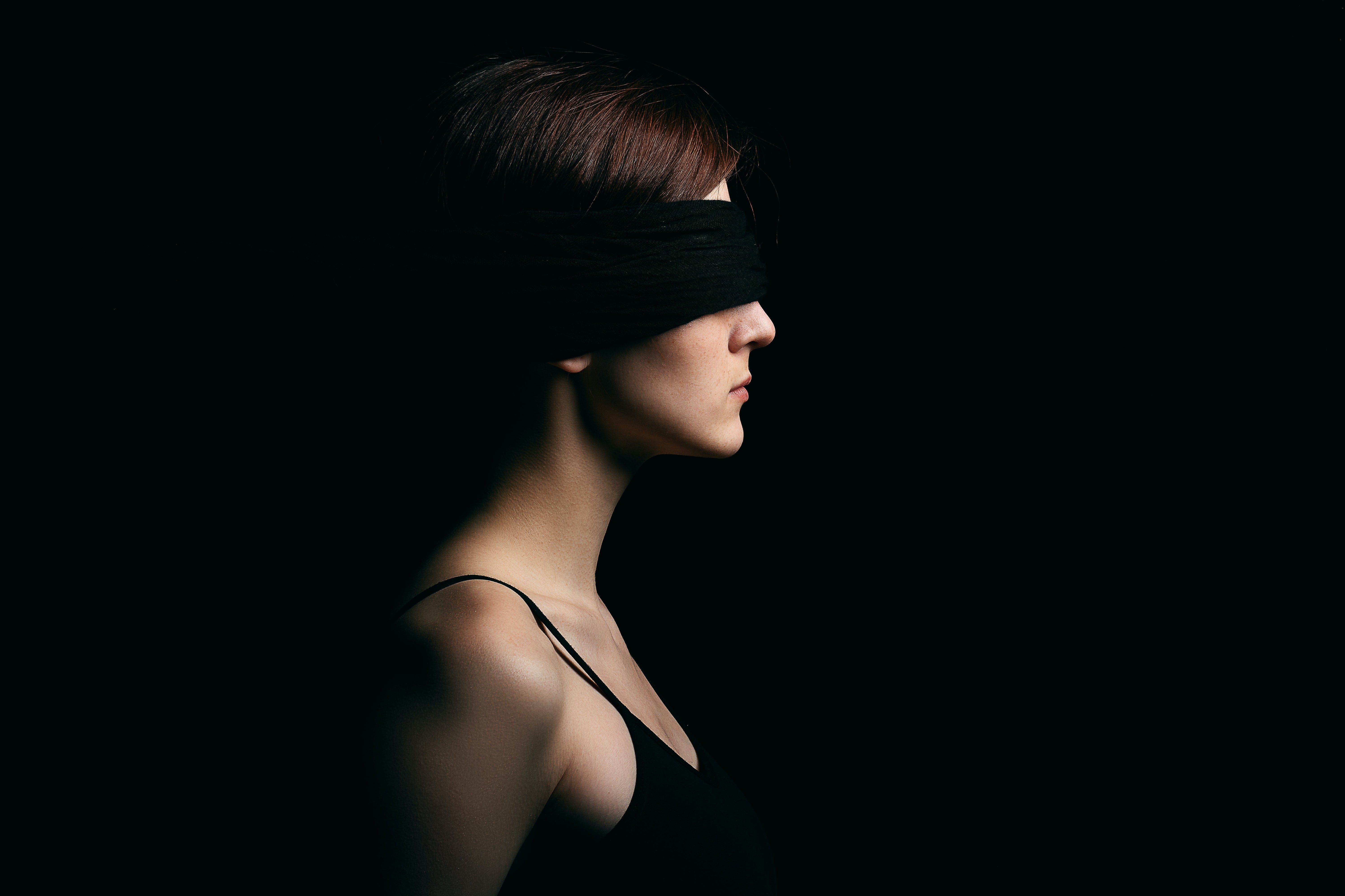 A blindfolded woman against black