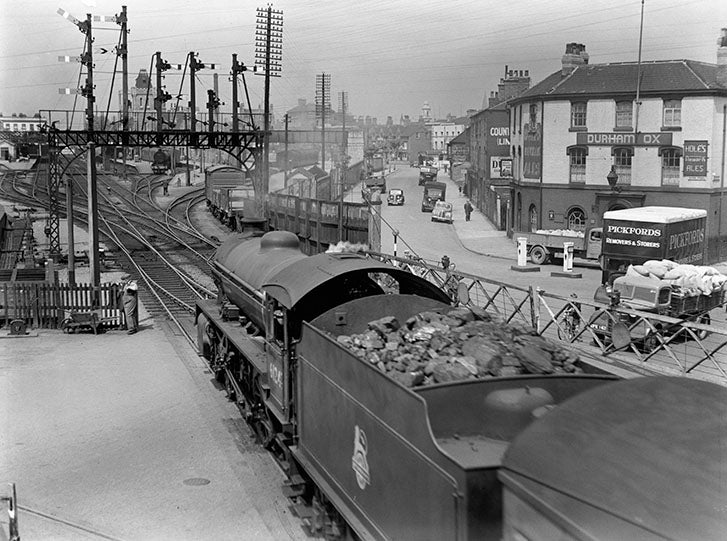 A black and white photo of Lincoln from the 1950s. A steam train is in the foreground