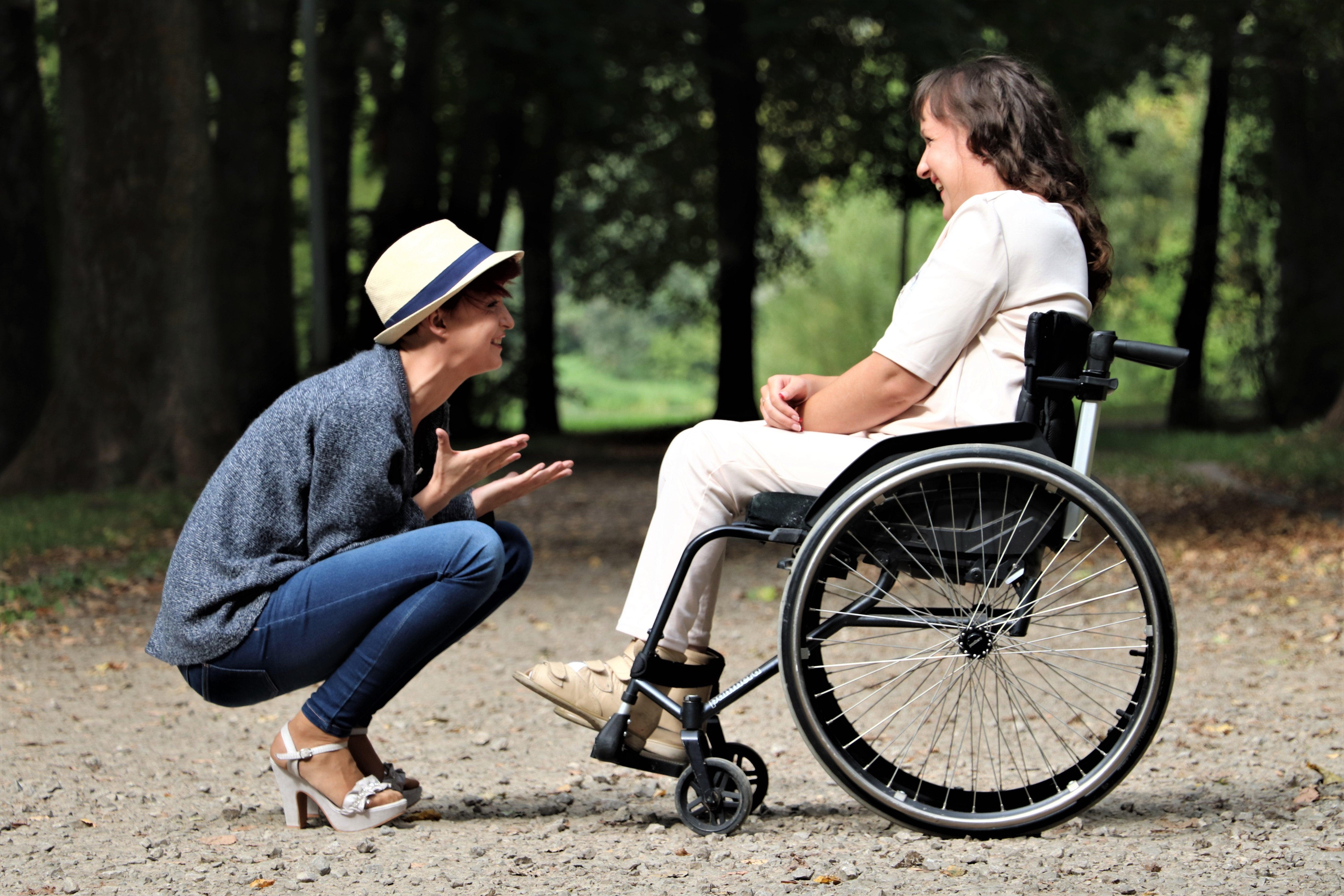 A woman talks to a female wheelchair user