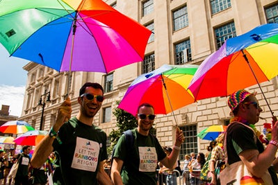 People holding rainbow umbrellas taking part in the London`s Gay Pride. they are smiling and wearing t-shirts with pride slogans on them