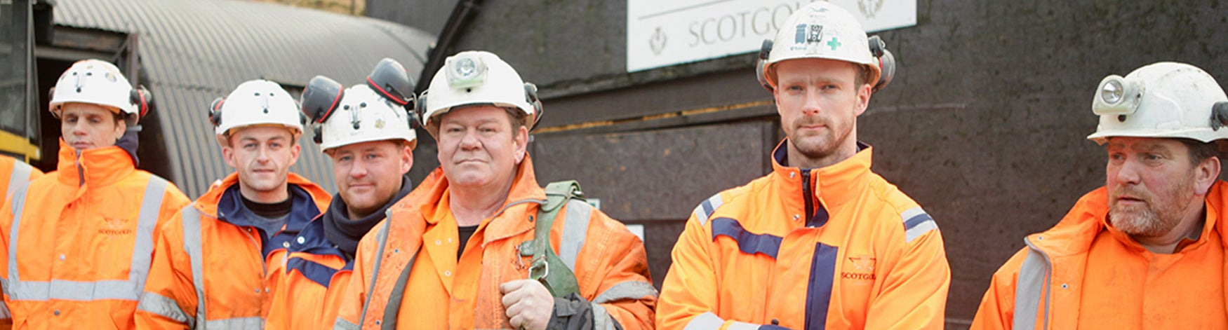 Miners stand in front of gold mine - bbc gold town