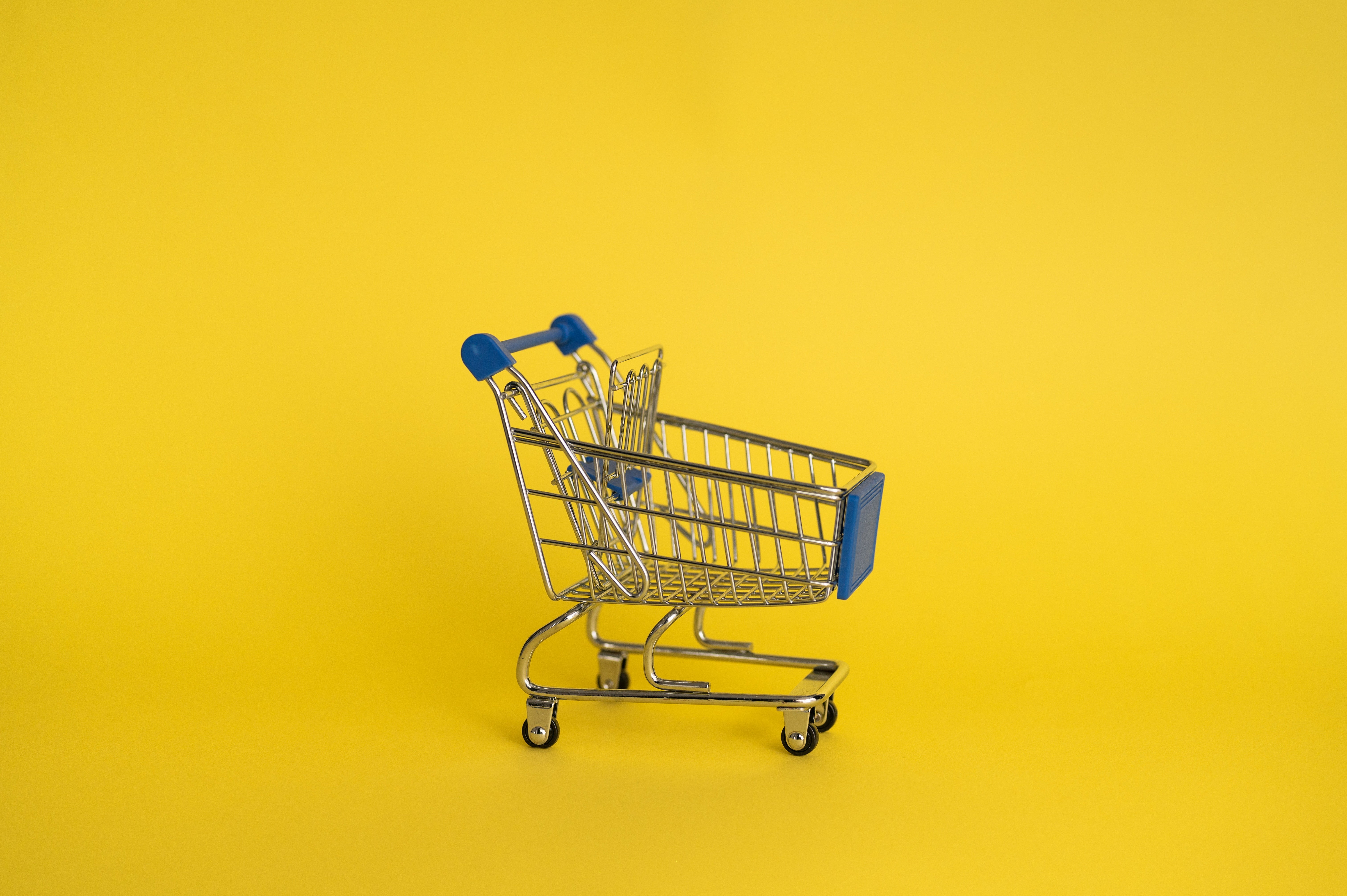 A toy shopping trolley on yellow