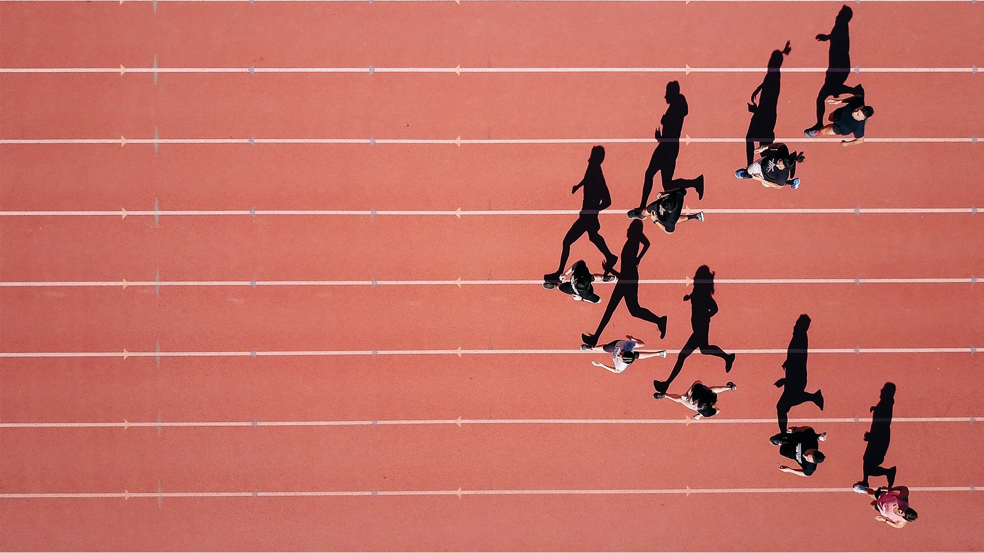 An aerial view of eight runners on a track, in a 'V' formation