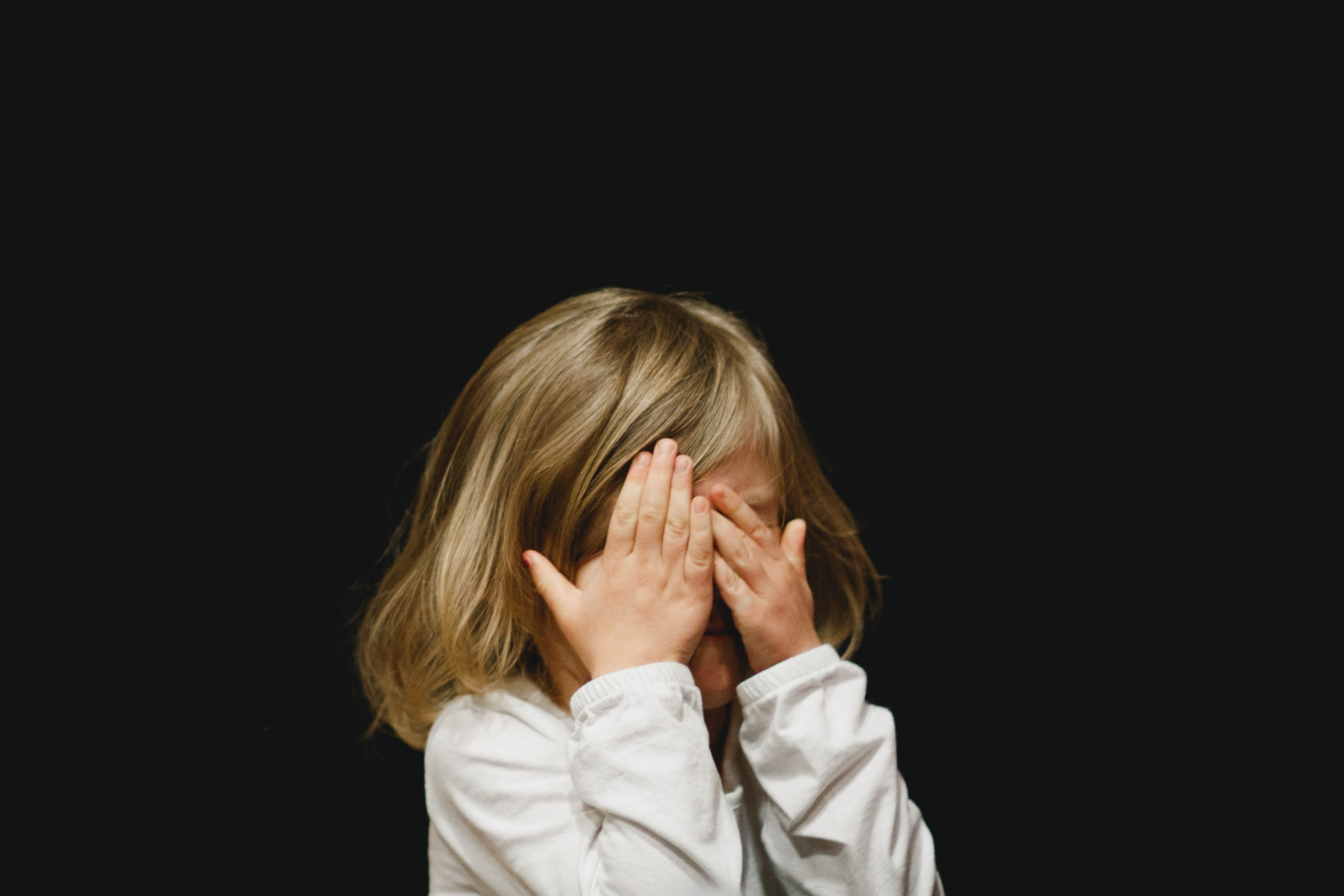 Young girl with her hands over her eyes