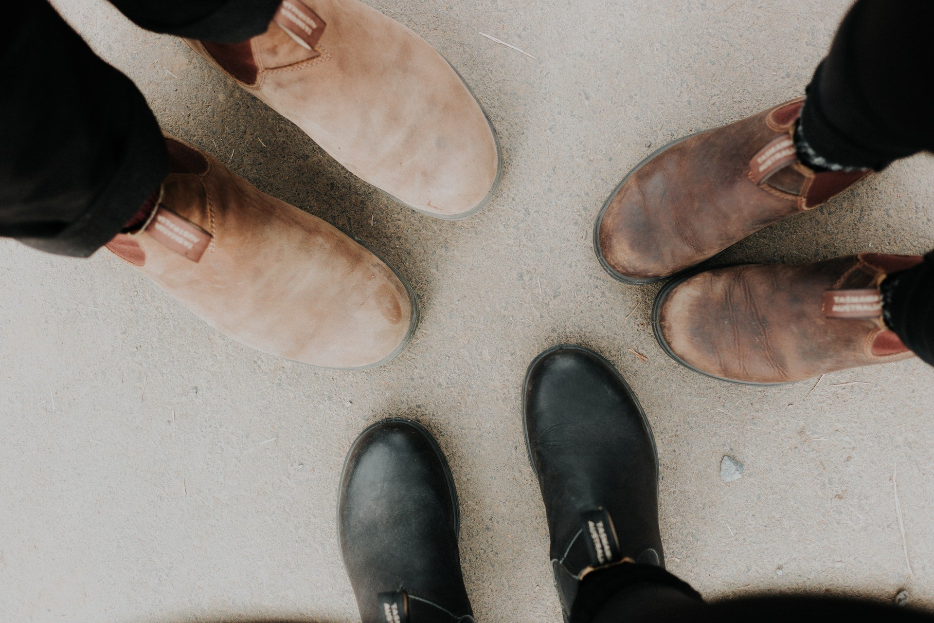 A photo of three people standing in a small circle, the camera is pointed at their shoes
