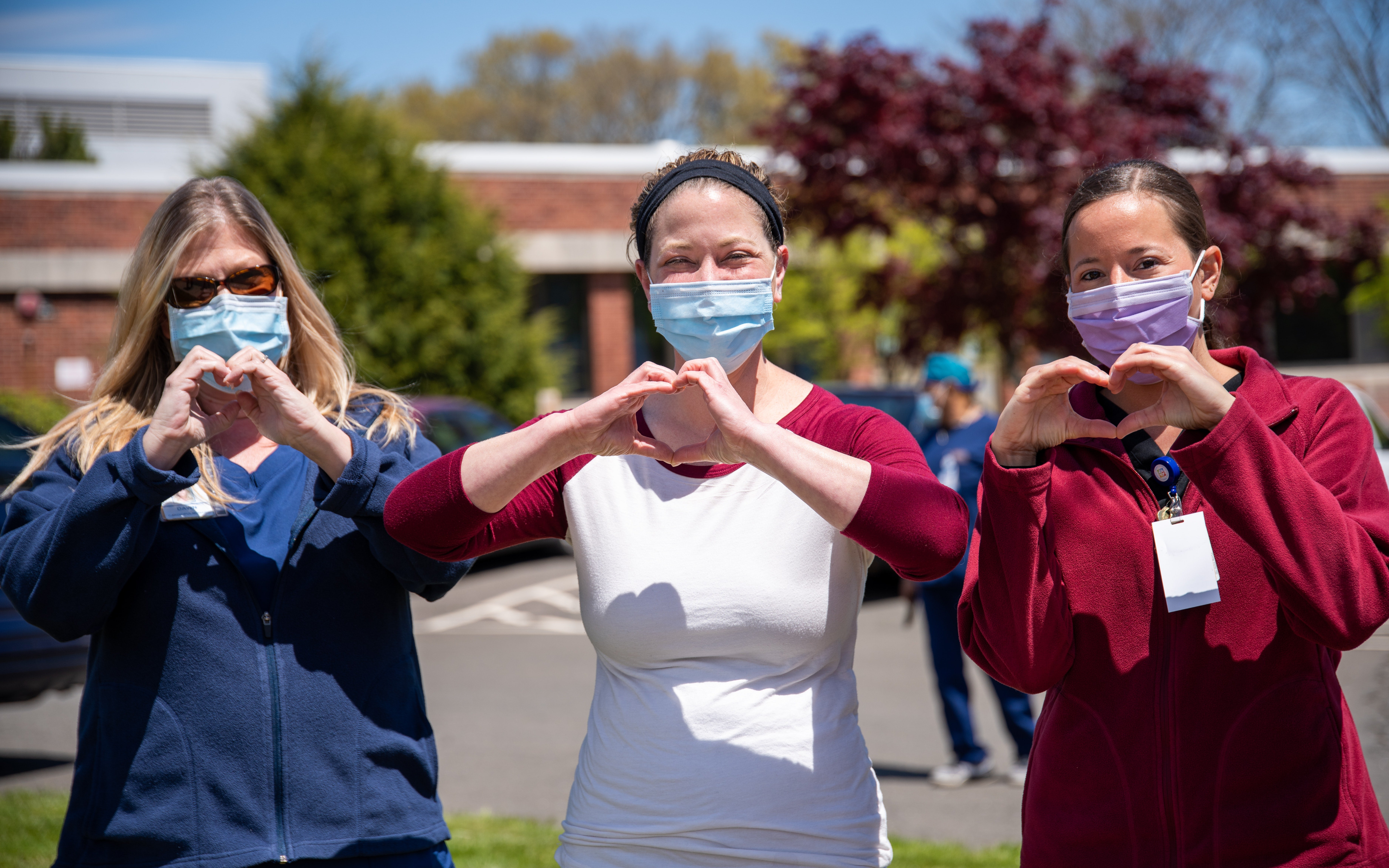 Nurses at Manchester Hospital during COVID, making heart shapes with their hands