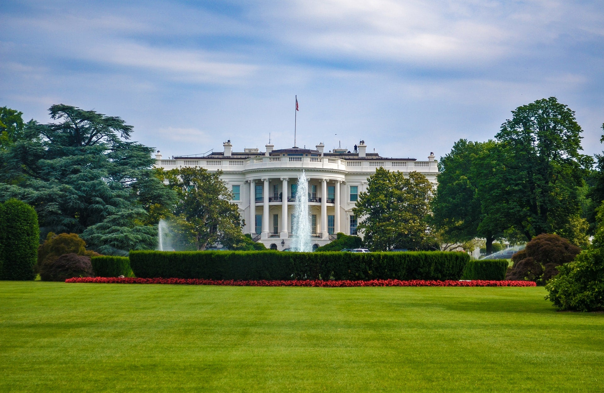 A photograph of The White House, with its green lawn in the foreground