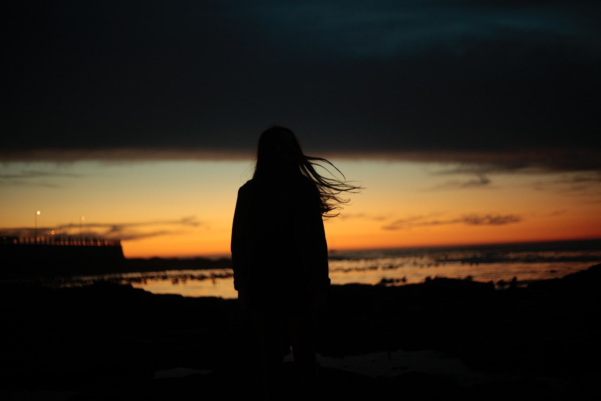 A picture of a girl looking out across the sea as the light is fading