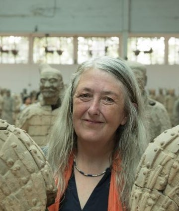 Mary Beard standing among Terracotta Army statues