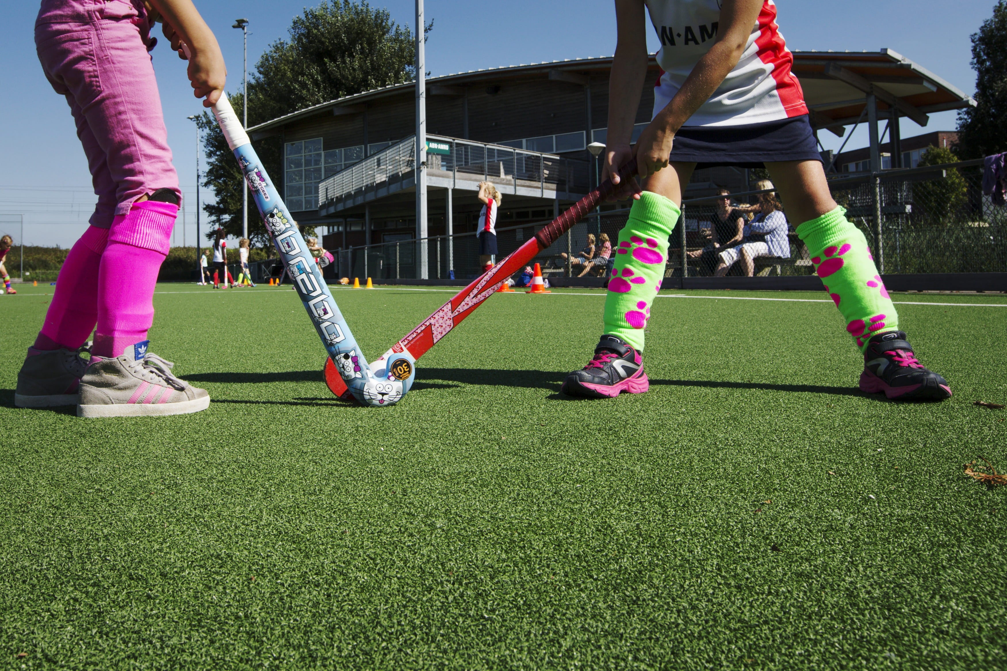 A photograph from ground level of two children holding hockey sticks, about to start a game
