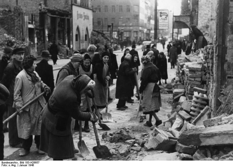 Black and white world war 2 photo of women in the street with shovels moving rubble