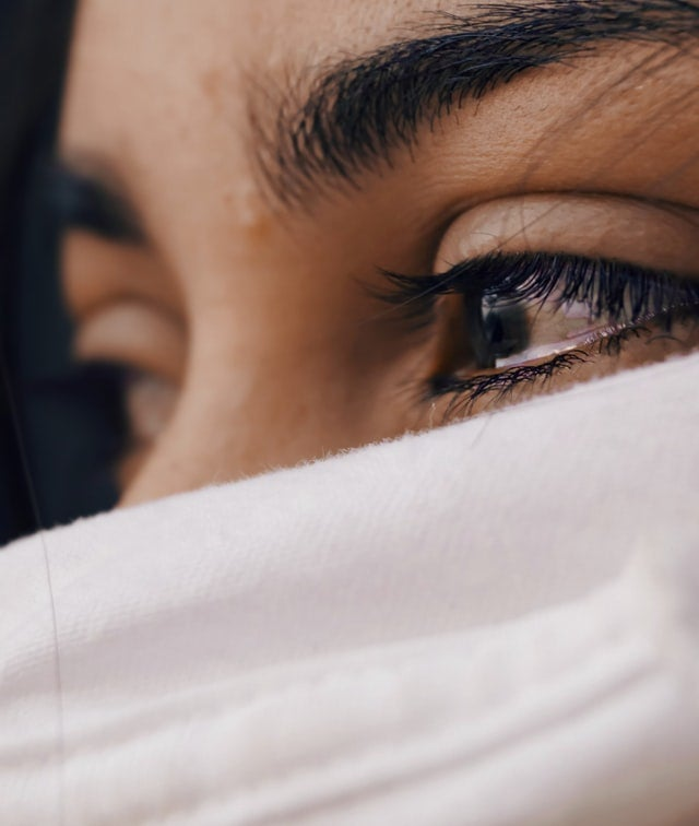 A close-up picture of a woman with a face covering. There are tears welling up in her eyes