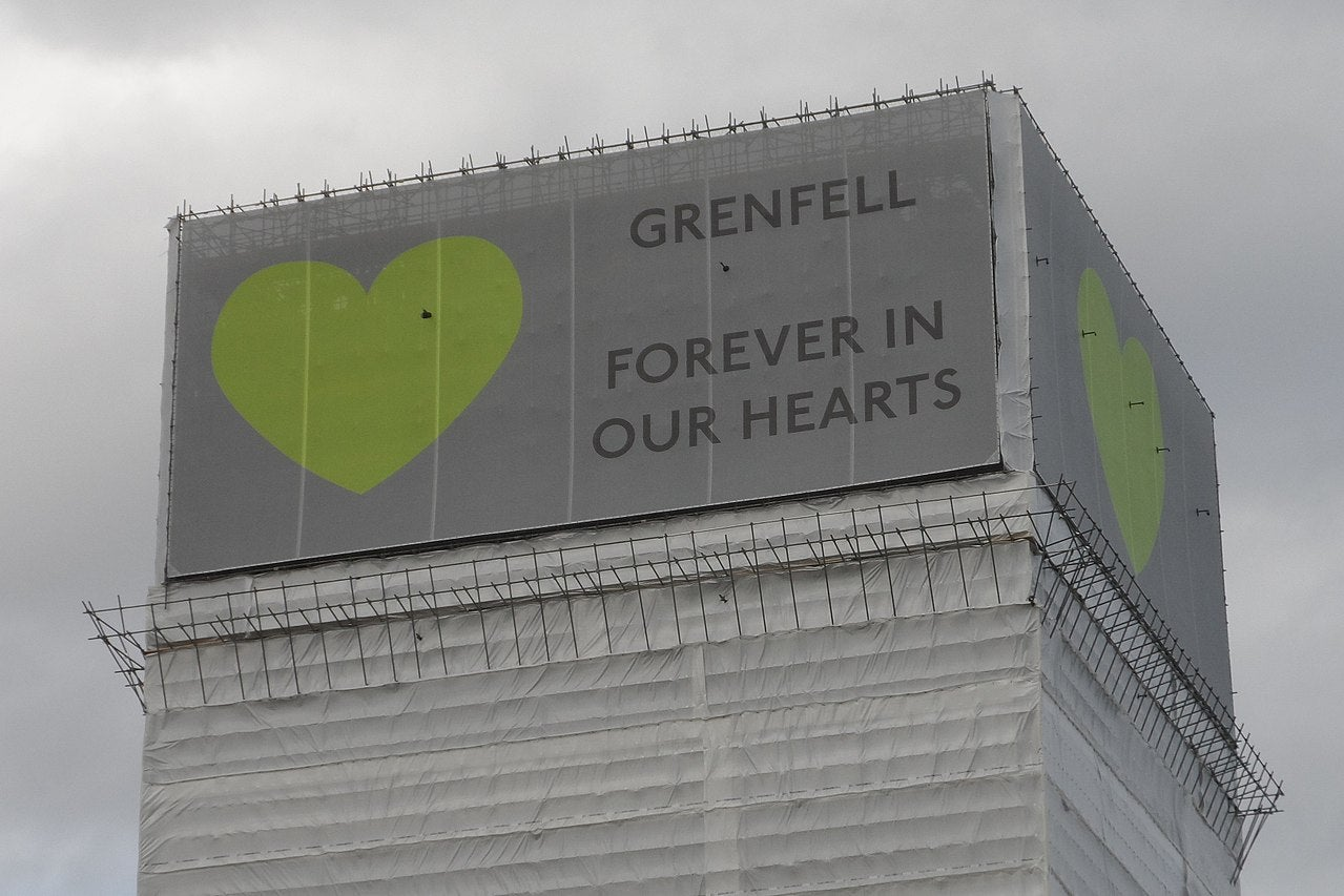 Grenfell tower after the fire, with a banner, reading forever in our hearts