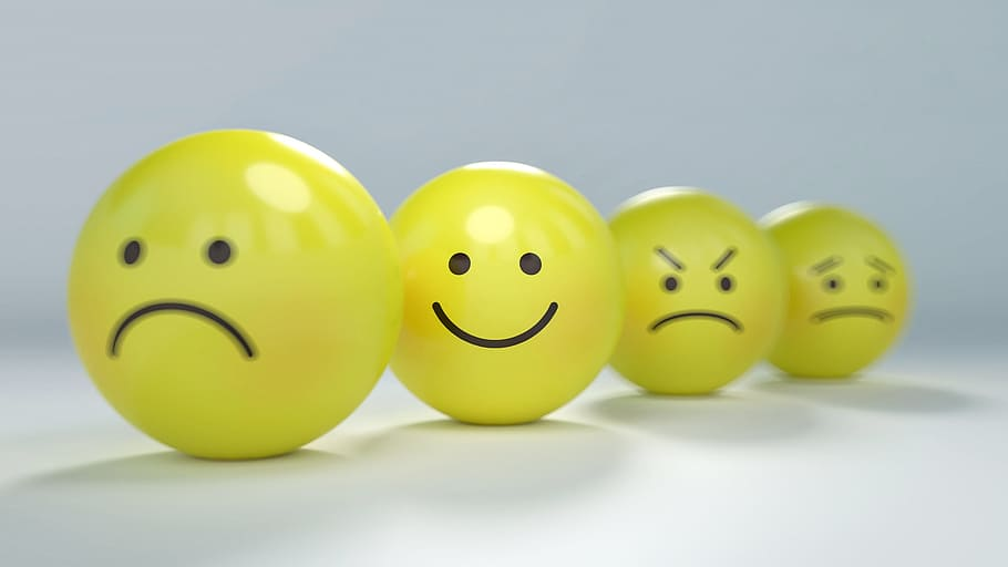 """Four yellow balls with expressions drawn on them in a """"smiley"""" style. They seem to represent sadness, happiness, anger and disappointment"""