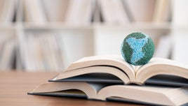 A picture with two open books on a desk. Perched on the top book is a small globe depicting planet Earth.