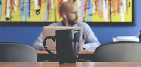 A photograph taken in a cafe. A mug is in focus in the foreground, and a man using a laptop is out of focus in the background.