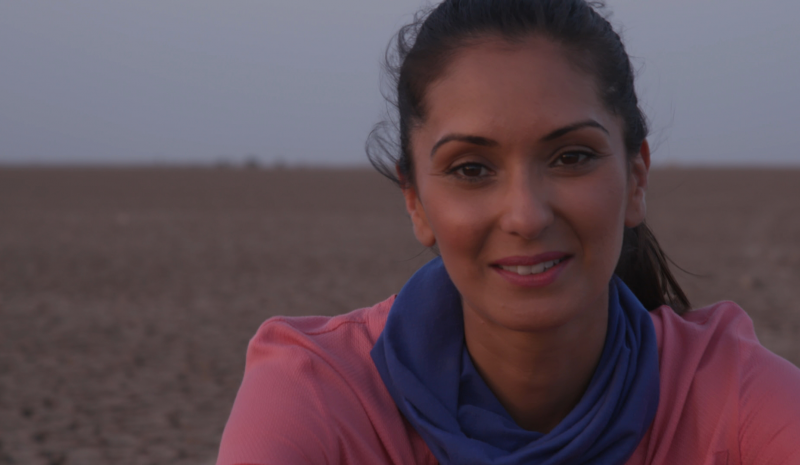 A photograph of Babita Sharma, a desert stretching out behind her