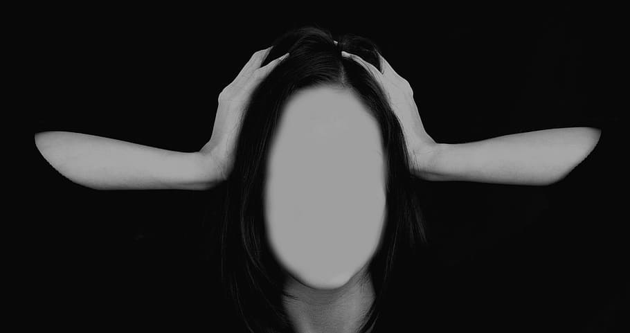 A woman with her hands pressed against the sides of her head. All of her facial features have been edited away, so she appears faceless.