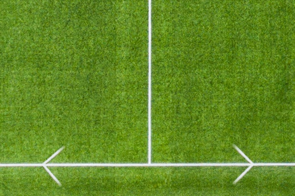 Two white arrows pulling away from each other on a football pitch