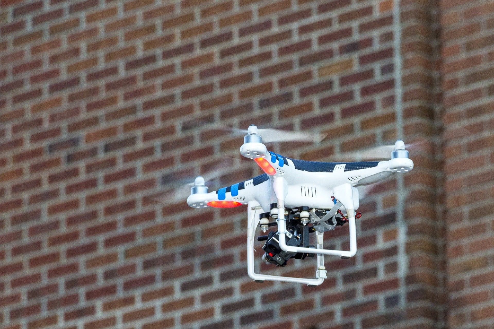 A drone files next to the brick wall of a building