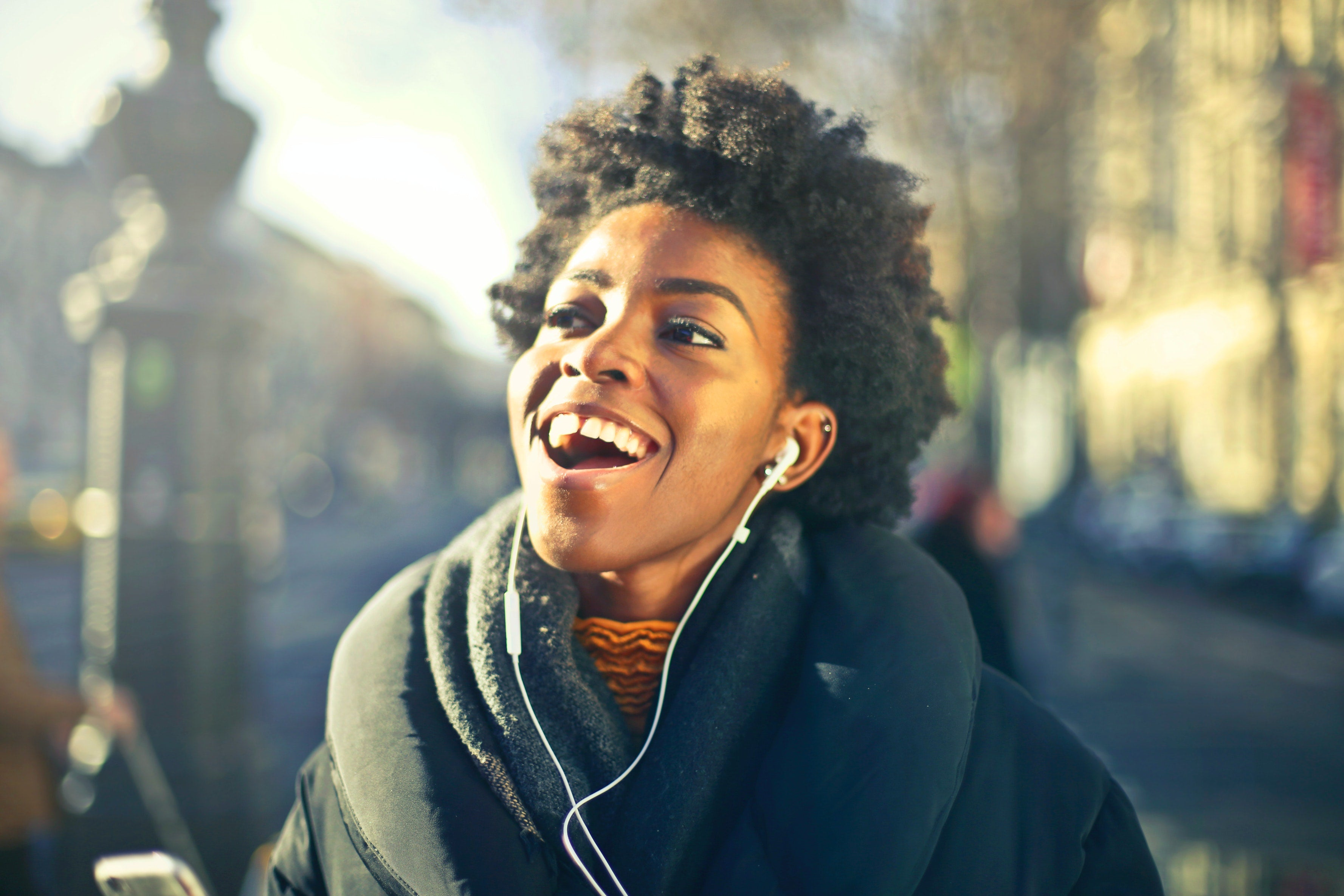 A woman joyfully listening to music on a walk
